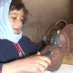 Afghan girl receiving a teddy bear in a school.