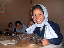 Closeup of girl in Afghanistan school receiving a fair trade teddy bear.