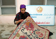 Afghani woman demonstrates how this rug is handmade.