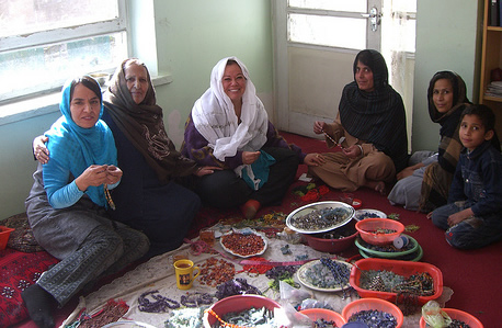 Group of Afghan women crafting necklaces, earrings and bracelets.
