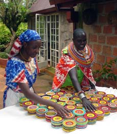 Kenyan women admire the beaded boxes they've crafted of high quality Czech beads.