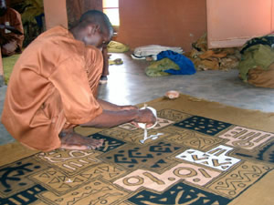 Man from Mali, Africa creating designs on bogolan or mud cloth.