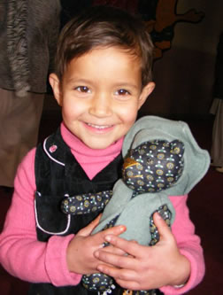 Happy young Afghanistan girl with her first teddy bear.