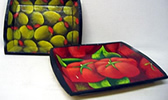 Olives and tomatoes decorate these wooden trays from El Salvador.