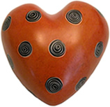 Orange soapstone heart with spirals from Kenya, Africa.