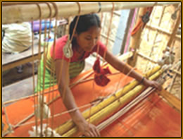 Indian woman at loom, weaving cloth for handbags.